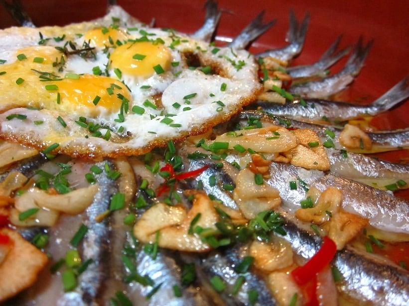 Boquerones al horno con refrito de ajos y huevos de codorniz cerca