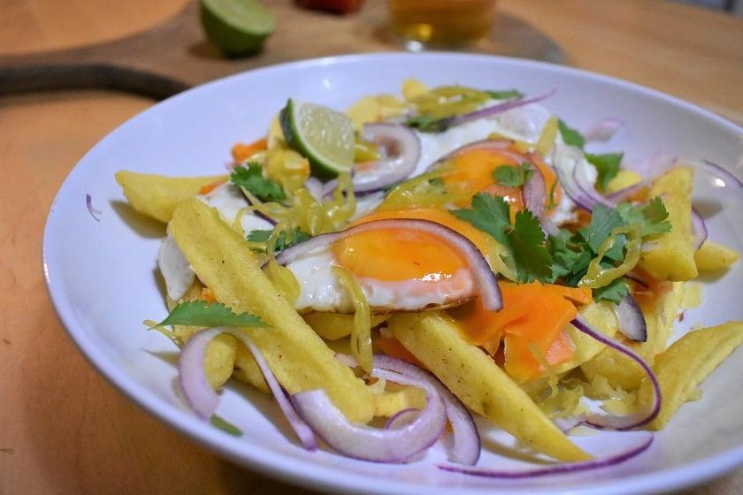 Huevos rotos con queso y cilantro