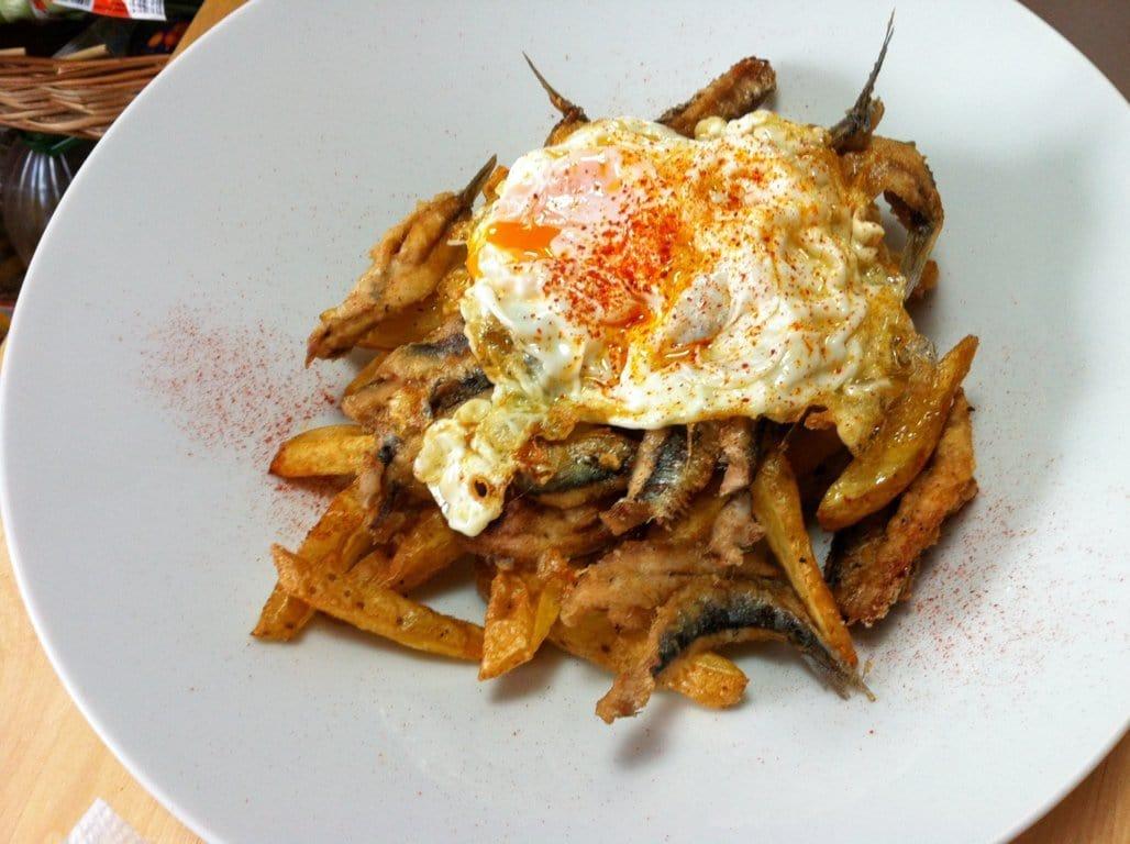 Huevos rotos con boquerones fritos